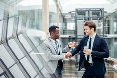 Un handshake multirazziale di due uomini d'affari in ufficio moderno per la conclusione di grande affare fotografia stock