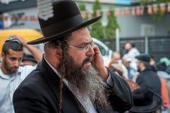 Un Hasid mayor en el sombrero judío tradicional que habla en el teléfono Imagenes de archivo