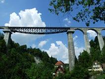Un haut pont en rail à travers la garde d'enfants de rivière images stock
