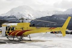 Un helicóptero amarillo en las montañas nevosas Suiza en invierno imagenes de archivo