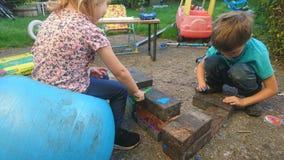 Un hermano y una hermana que juegan con los ladrillos y la masilla de los constructores imagen de archivo