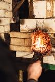 Un herrero enciende un fuego en el horno fotos de archivo