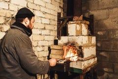 Un herrero enciende un fuego en el horno imagen de archivo libre de regalías