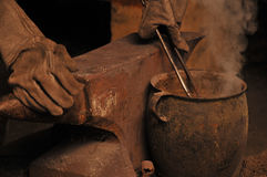 Un herrero que refresca una herradura en un pote imagen de archivo libre de regalías