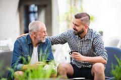 Un hijo adulto del inconformista y un padre mayor con una taza de café en un café al aire libre Fotos de archivo