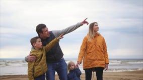 Un hijo joven está señalando lejos en cierto objeto, una familia amistosa está observando almacen de metraje de vídeo