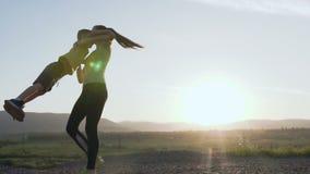 Un hijo y una madre felices Una mujer feliz del deporte juega con el niño en la naturaleza en la puesta del sol después de entren metrajes