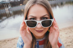 Un hippy de la muchacha en la orilla del río que presenta y que sonríe fotografía de archivo libre de regalías