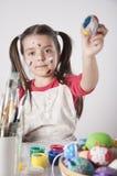 Un holdin heureux de petite fille a peint des oeufs de pâques Photographie stock libre de droits