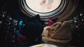 Un hombre abre la puerta y carga el lavadero en la lavadora almacen de video