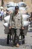 Un hombre acarrea una carga pesada de sacos a través bazar del ili de Khan el Khal ' en El Cairo, Egipto imágenes de archivo libres de regalías