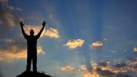 Un hombre adora a dios silueteado contra una puesta del sol almacen de video
