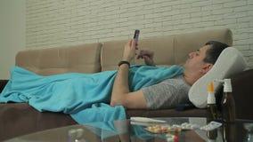 Un hombre adulto con las muestras de un frío miente, envuelto en una manta en el sofá y sostener un teléfono móvil almacen de metraje de vídeo
