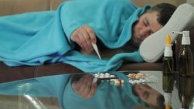 Un hombre adulto con síntomas de la enfermedad duerme en el sofá con el pretexto de una manta almacen de video