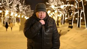 Un hombre adulto joven en calle de la ciudad del invierno Él congela, frota sus manos y escalofríos del frío almacen de video