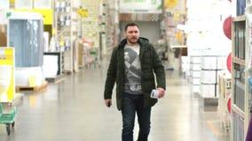 Un hombre adulto joven en una chaqueta verde está caminando a lo largo de una tienda 4K de la construcción metrajes