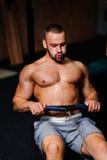 Un hombre adulto muscular que hace ejercicios en un simulador en un fondo del gimnasio Aptitud, deportes, y concepto sano de la f Imagen de archivo