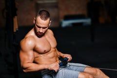 Un hombre adulto muscular que hace ejercicios en un simulador en un fondo del gimnasio Aptitud, deportes, y concepto sano de la f Imagenes de archivo