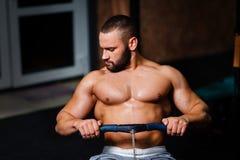 Un hombre adulto muscular que hace ejercicios en un simulador en un fondo del gimnasio Aptitud, deportes, y concepto sano de la f Fotografía de archivo libre de regalías