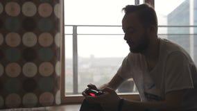 Un hombre adulto sostiene la palanca de mando del juego en manos de la ventana almacen de metraje de vídeo