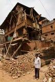 Un hombre ahora se coloca fuera de su casa arruinada terremoto en Bhaktapu Foto de archivo