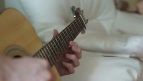 Un hombre ajusta las secuencias de la guitarra metrajes
