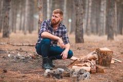 Un hombre al lado de la madera en la tierra mira lejos en el bosque del otoño Imagen de archivo