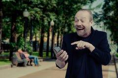 Un hombre alegre, barbudo, blanco está hablando en el teléfono foto de archivo