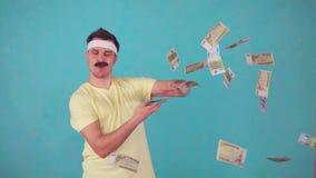 Un hombre alegre con un bigote mira la cámara y lanza un paquete de dinero metrajes