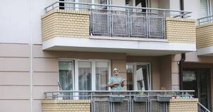 Un hombre alegre con una barba juega el ukelele en el balcón almacen de metraje de vídeo