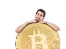 Un hombre alegre con una sonrisa alegre grande que celebra una moneda enorme del bitcoin en un fondo blanco Fotos de archivo