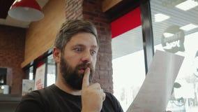Un hombre alegre, joven con una barba lee el menú y hace una orden en la barra almacen de metraje de vídeo