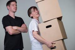 Un hombre apenas está mirando mientras que una mujer está llevando cardboxes pesados Imagen de archivo libre de regalías