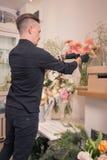 Un hombre, arreglando las flores, floristería, dentro Foto de archivo