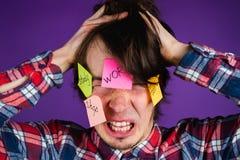 Un hombre ase su cabeza y gritos, un retrato del primer Sus obligaciones y rutina choca a un hombre Etiquetas engomadas en cara Fotos de archivo libres de regalías