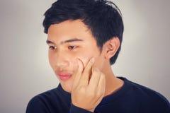 Un hombre asiático está exprimiendo acné en su cara con el vintage fotos de archivo