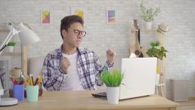 Un hombre asiático joven en vidrios elegantes consiguió un triunfo disfruta y baila detrás de un ordenador portátil en la sala de almacen de video