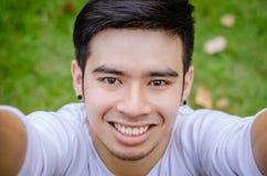 Un hombre asiático joven sonriente que hace la foto del selfie Fotografía de archivo libre de regalías