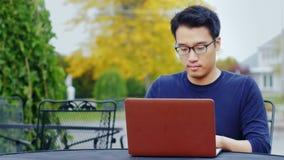 Un hombre asiático joven trabaja con un ordenador portátil El sentarse al aire libre en una ciudad americana típica metrajes