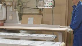 Un hombre asierra los espacios en blanco de madera en la máquina, la producción de la puerta de puertas interiores del pueblo almacen de video
