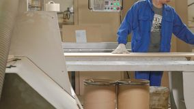Un hombre asierra los espacios en blanco de madera en la máquina, la producción de la puerta de puertas interiores del pueblo metrajes