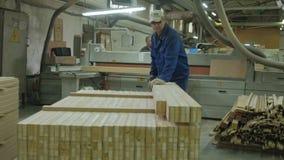 Un hombre asierra los espacios en blanco de madera en la máquina, la producción de la puerta de puertas interiores del pueblo almacen de metraje de vídeo