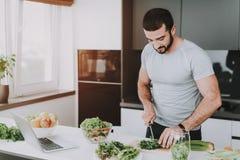 Un hombre atlético está preparando la ensalada para el desayuno fotografía de archivo