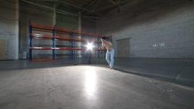 Un hombre atlético que hace elementos difíciles del capoeira en el cuarto con el piso y las paredes de ladrillo concretos metrajes