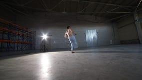 Un hombre atlético que hace elementos y saltos del capoeira en el cuarto con el piso y las paredes de ladrillo concretos almacen de video
