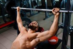 Un hombre atractivo con un cuerpo muscular realiza una prensa de banco usando un barbell en un fondo oscuro borroso Fotografía de archivo
