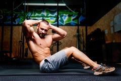 Un hombre atractivo que hace un ejercicio en un piso y en un fondo de un gimnasio Concepto de los deportes, del entrenamiento y d Imagen de archivo libre de regalías