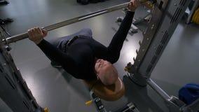 Un hombre aumenta un barbell pesado mismo 4K MES lento almacen de video
