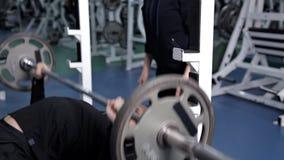Un hombre aumenta la barra que trabaja en el gimnasio almacen de metraje de vídeo