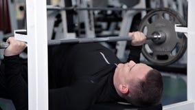 Un hombre aumenta la barra que trabaja en el gimnasio almacen de video